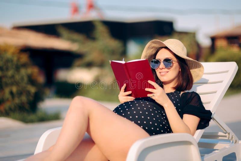 Беременная женщина читая книгу бассейном стоковая фотография rf