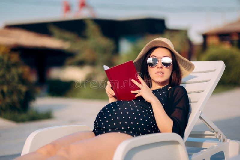Беременная женщина читая книгу бассейном стоковое фото