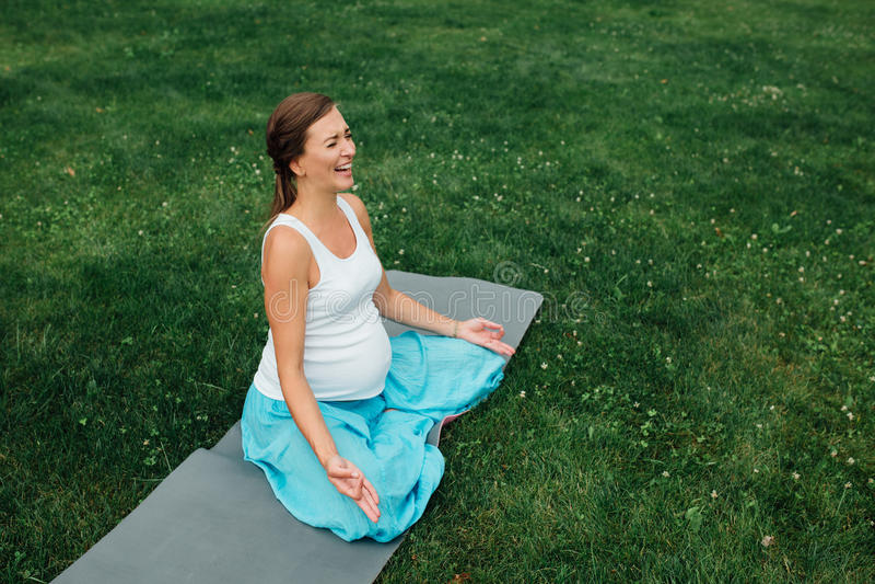Беременная йога в положении лотоса на предпосылке леса в парке циновка травы, внешняя, женщина здоровья стоковые фотографии rf