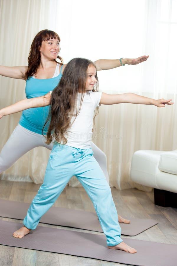 Беременная мама делая пренатальную йогу с ее маленькой дочерью на hom стоковое изображение