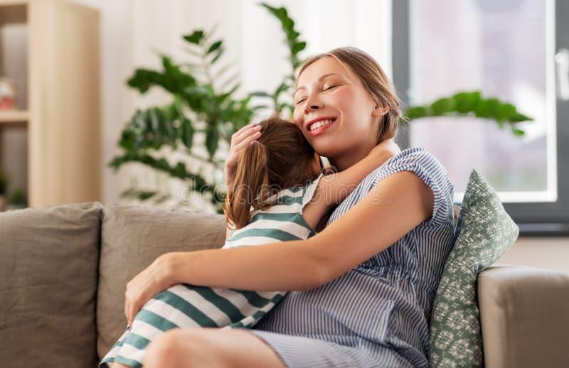 Беременная мать и дочь обнимая дома стоковые изображения rf