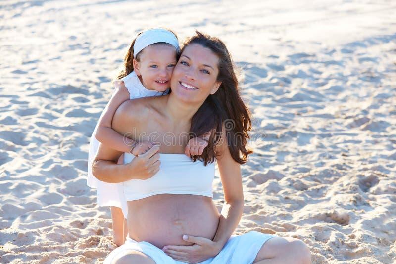 Беременная мать и дочь на пляже стоковые изображения rf