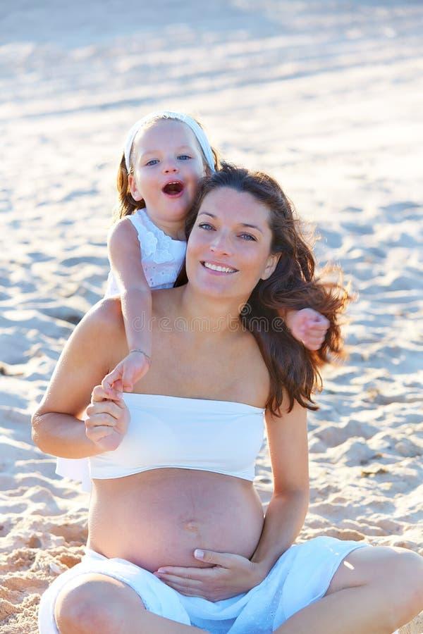 Беременная мать и дочь на пляже стоковые фото