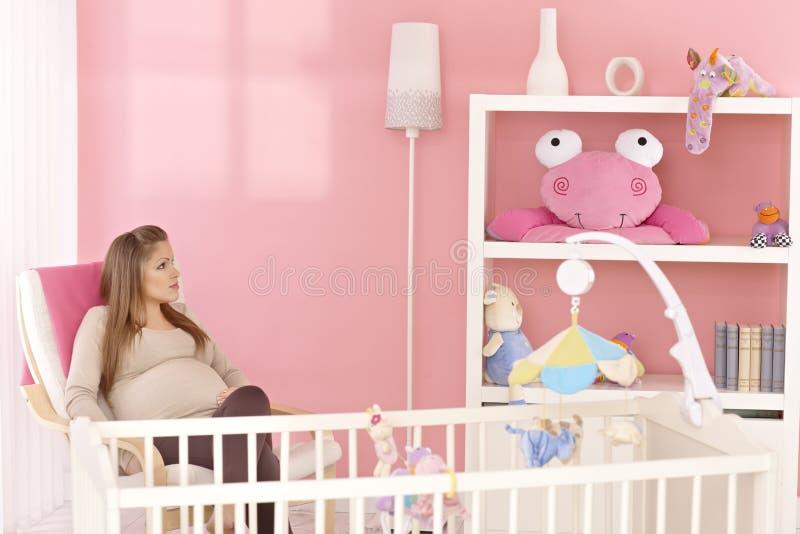 Беременная мать сидя в комнате младенца стоковое фото rf