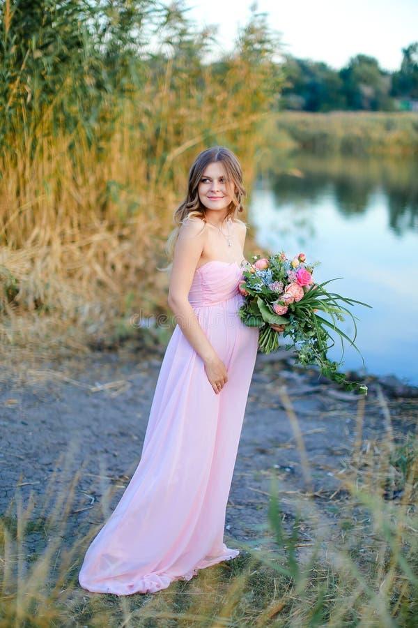 Беременная молодая женщина нося розовое платье с букетом цветков стоя близко озеро стоковая фотография