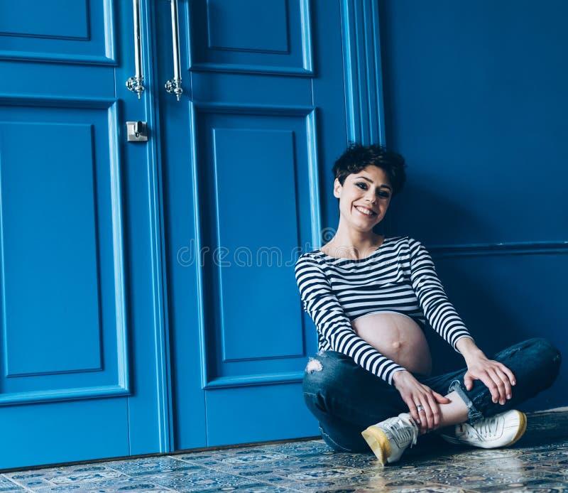 Беременная усмехаясь женщина сидя на деревянном поле в комнате материнствй материнство стоковая фотография