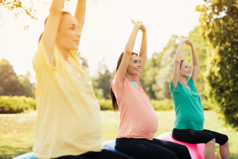 3 беременной женщины сидят в парке на шариках йоги с их руками вверх стоковое изображение rf