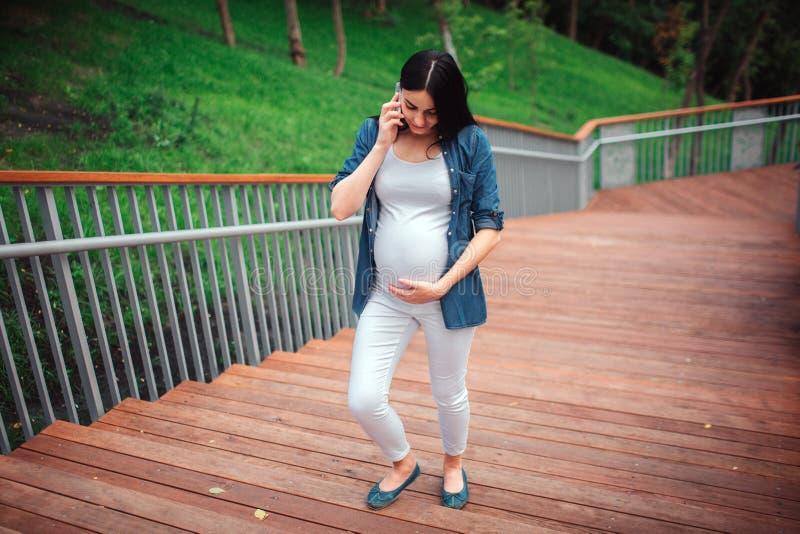 Беременность, материнство, люди и концепция ожидания - конец вверх беременной женщины с хозяйственными сумками на парке стоковые изображения
