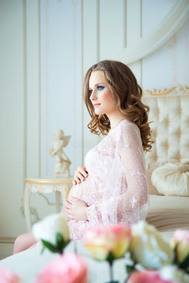Беременность, остатки, люди и концепция ожидания - счастливая беременная женщина сидя на кровати и касаясь ее животу дома стоковые изображения