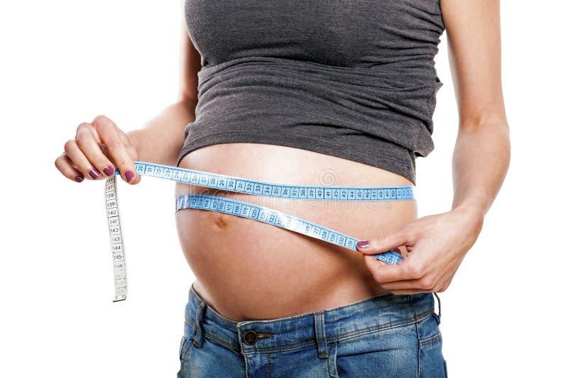 Беременный женский измеряя живот, часть тела стоковая фотография rf