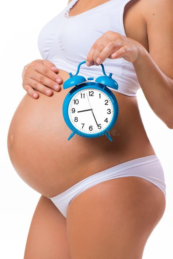 Беременный живот с будильником Схематическое изображение счастливой беременности стоковые фото