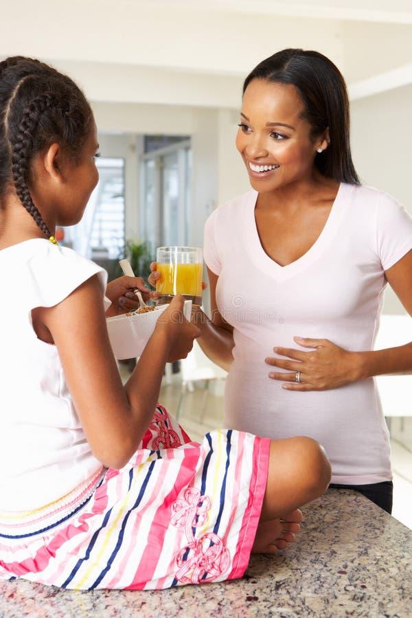 Беременный сок матери и дочери выпивая в кухне стоковые фото