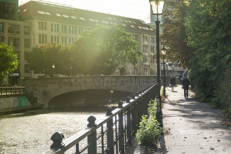БЕРЛИН, ГЕРМАНИЯ - 28-ое июля 2018: Мирный свет утра над античным мостом, прежними зданиями, и наполненным дерев стоковое изображение rf