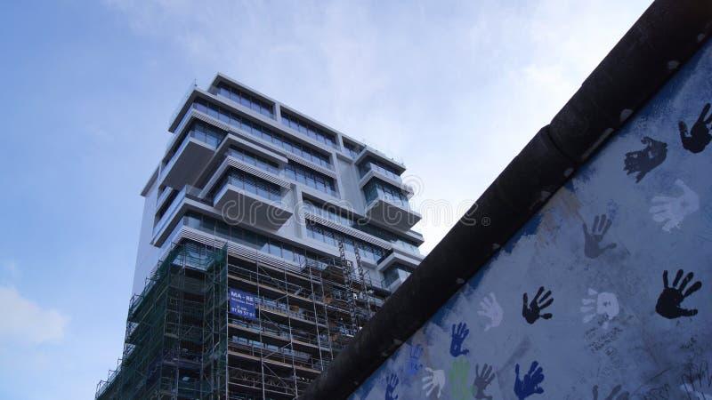 БЕРЛИН, ГЕРМАНИЯ - 17-ое января 2015: Берлинская стена и новый высокий жилой дом подъема на галерее Ист-Сайд стоковое фото