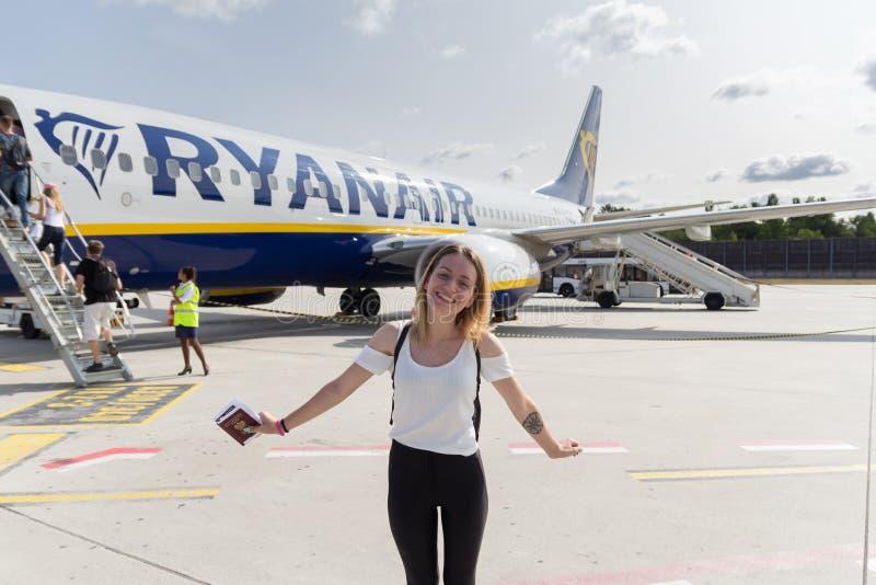 08 21 2018 - Берлин Tegel, Германия: Красивая молодая женщина с паспортом стоя и усмехаясь перед самолетом Ryanair дальше стоковые фото