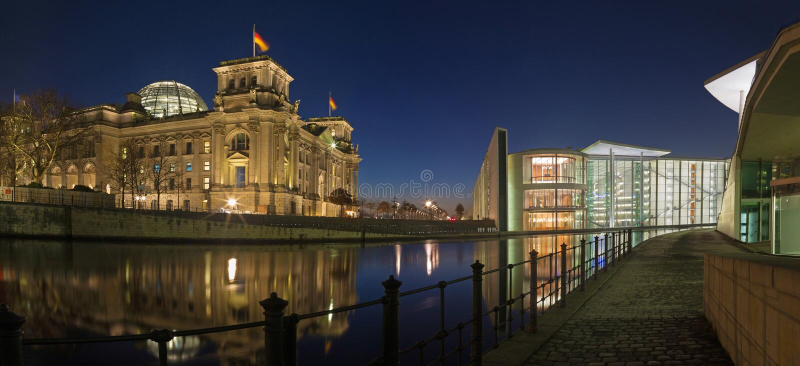 Берлин - панорама современных зданий и Reichstag правительства над рекой оживления в сумраке вечера стоковые фотографии rf