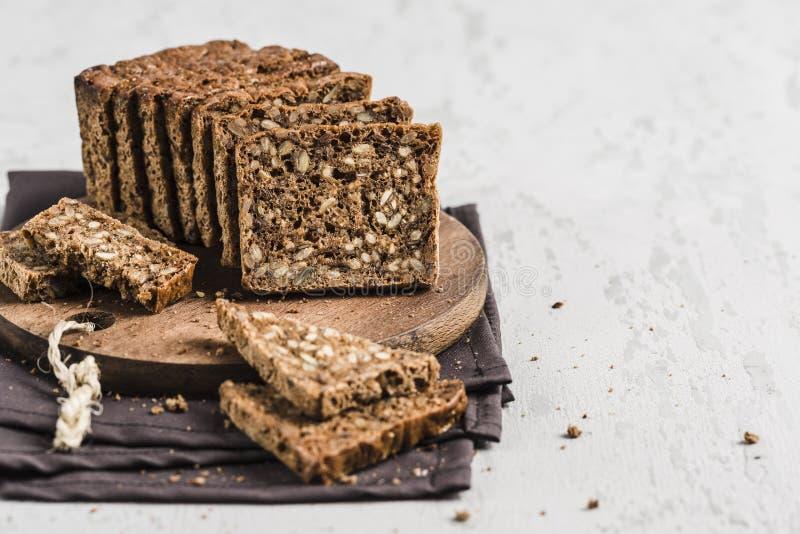 Бесглютеновый хлеб с ореховым орехом и семенами льняков на деревянной  стоковые изображения rf