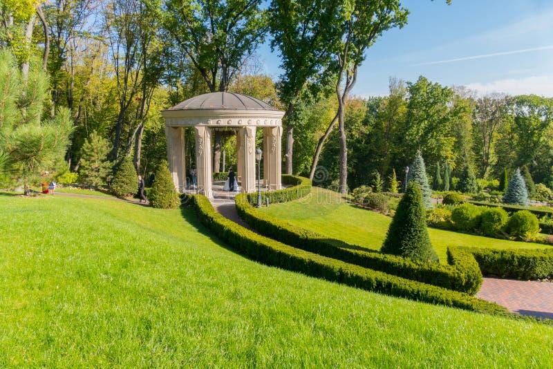 Беседка с красивыми, прерванными creslons в зеленом цвете, парком весны Идеальное место для фотосессии свадьбы Какой парень и стоковая фотография