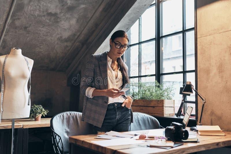 Беседовать с клиентом Привлекательная молодая женщина в eyewear используя стоковое фото