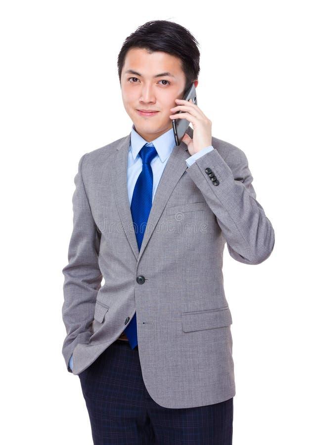 Беседа бизнесмена к мобильному телефону стоковые изображения rf