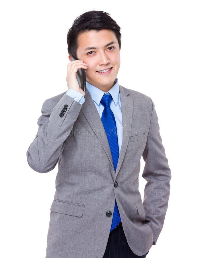 Беседа бизнесмена к мобильному телефону стоковое изображение
