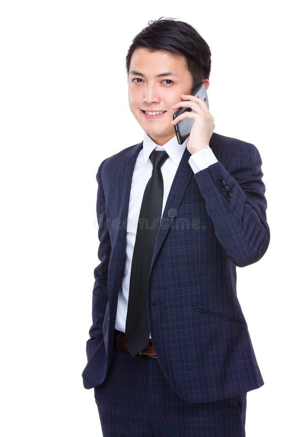 Беседа бизнесмена к сотовому телефону стоковое фото rf