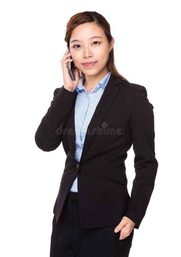 Беседа коммерсантки к мобильному телефону стоковое изображение rf
