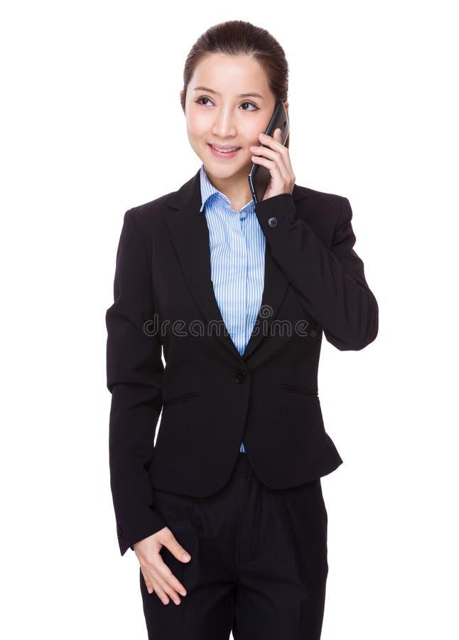 Беседа коммерсантки к мобильному телефону стоковая фотография