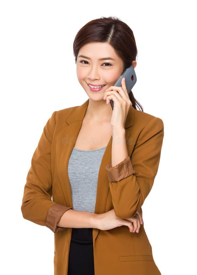 Беседа коммерсантки к мобильному телефону стоковые изображения