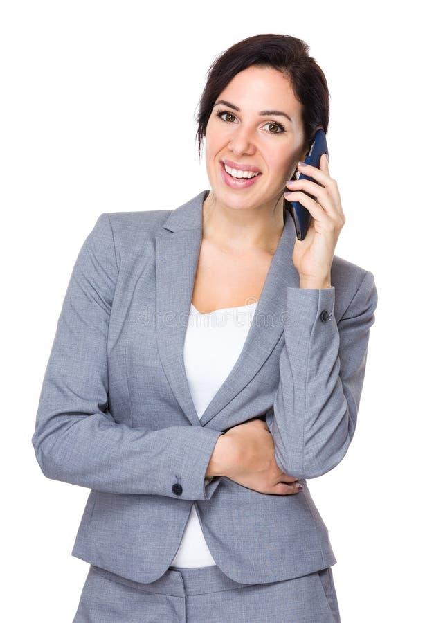 Беседа коммерсантки к мобильному телефону стоковое изображение