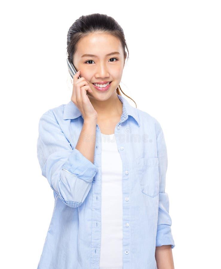 Беседа молодой женщины к мобильному телефону стоковое фото