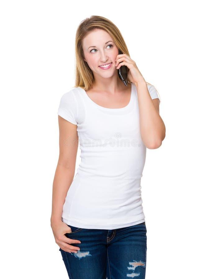 Беседа молодой женщины к мобильному телефону стоковые изображения