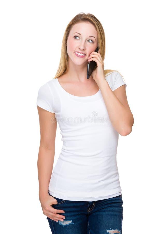 Беседа молодой женщины к сотовому телефону стоковое изображение