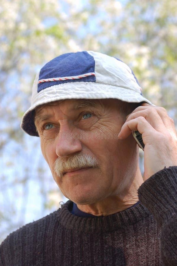 Беседа старшего человека в телефоне стоковая фотография