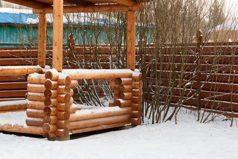 Беседка журнала в кустах в снеге стоковое изображение rf