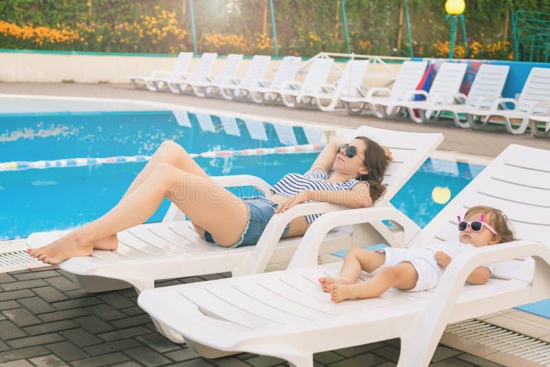 Бесконечное лето Милый младенец и мать ослабляя на sunbed стоковая фотография