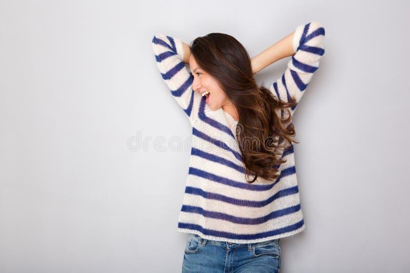Беспечальная молодая азиатская женщина смеясь с руками за головой против серой предпосылки стоковое фото rf