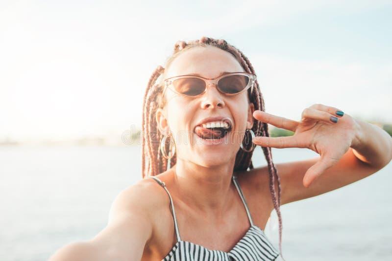 Беспечальная молодая женщина с африканскими оплетками делая selfie на пляже, время летних каникулов стоковое изображение