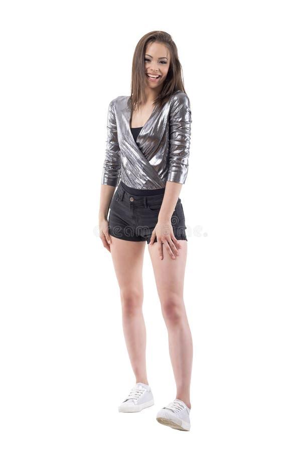 Беспечальная молодая красивая женщина смеясь над heartily самопроизвольно и смотря камеру стоковые изображения