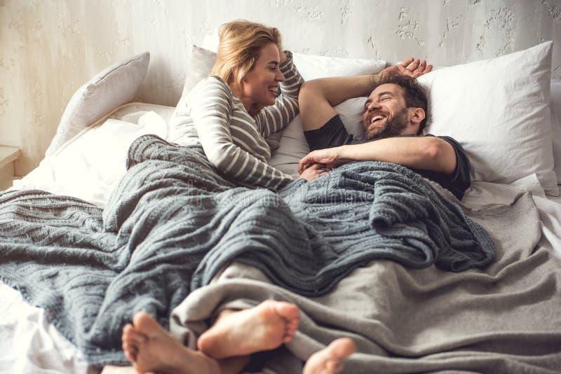 Беспечальная пара имеет потеху пока остающся в кровати стоковые фотографии rf