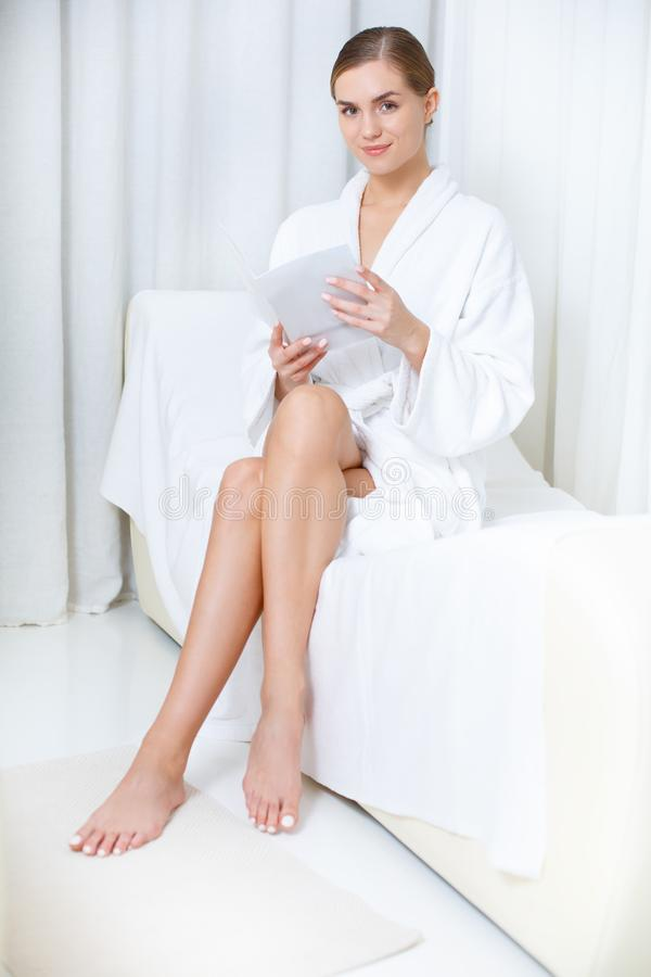 Беспечальный журнал чтения женщины в салоне курорта стоковое изображение rf