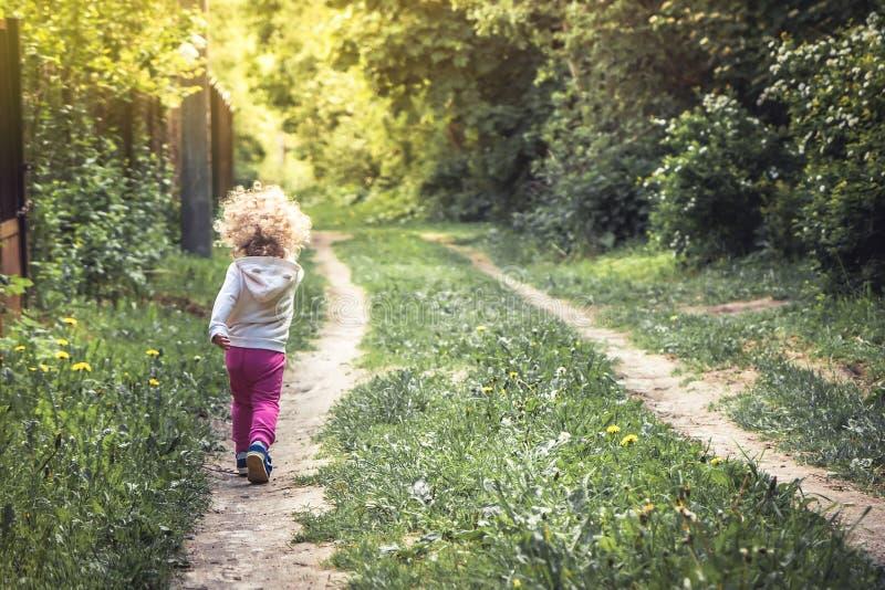 Беспечальное счастливое детство при шаловливый ребенок идя самостоятельно на сельскую тропу в лесе во время летних отпусков стоковое изображение rf