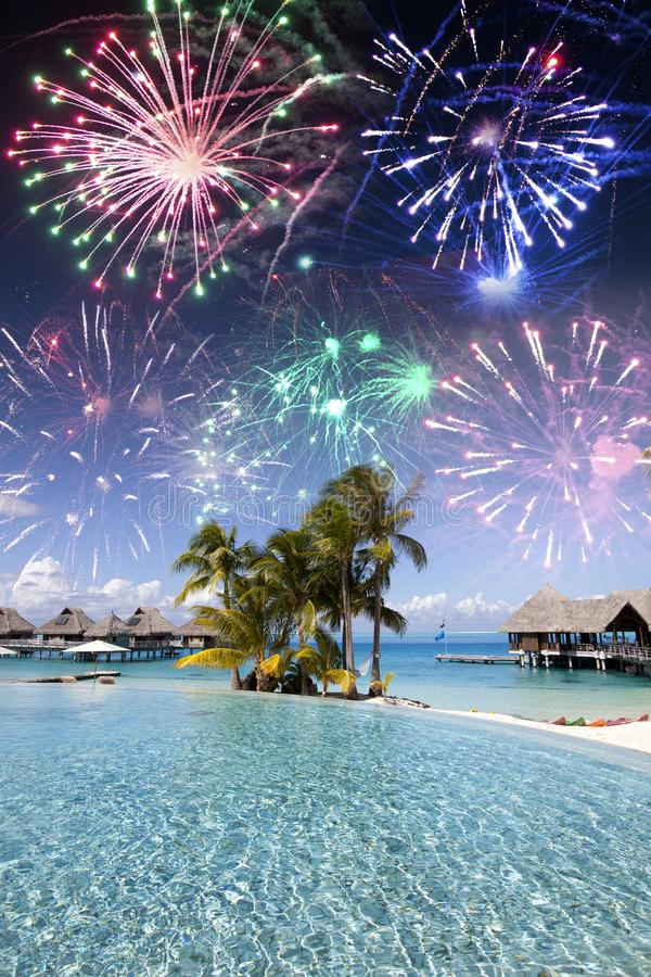 Беспечные новые годы фейерверки над тропическим островом, смешанные СМИ стоковые изображения