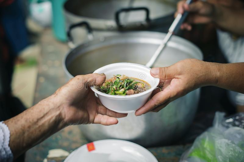 Беспризорность концепции: Потребности еды бедных в помощи общества с пожертвованием еды: Бездомные комплектуют вверх еду призрени стоковая фотография rf