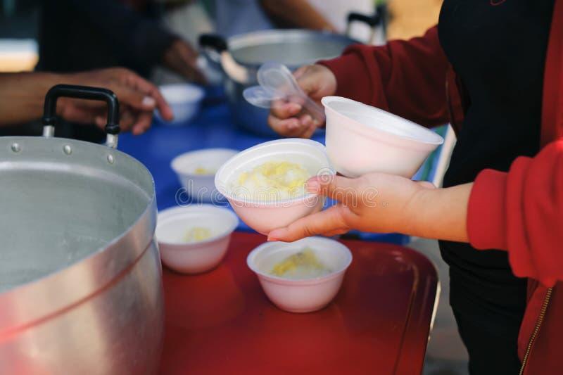 Беспризорность концепции: Потребности еды бедных в помощи общества с пожертвованием еды: Бездомные комплектуют вверх еду призрени стоковые изображения