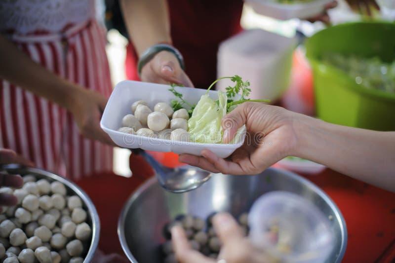 Беспризорность концепции: Потребности еды бедных в помощи общества с пожертвованием еды: Бездомные комплектуют вверх еду призрени стоковая фотография