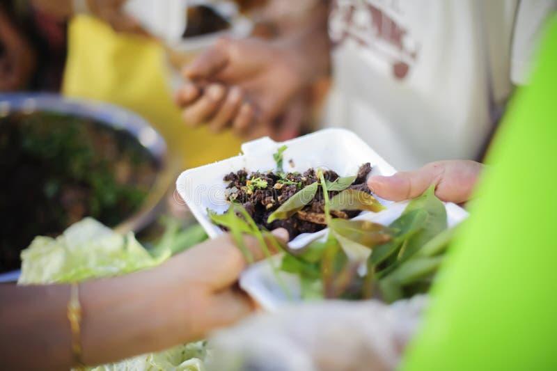 Беспризорность концепции: Потребности еды бедных в помощи общества с пожертвованием еды: Бездомные комплектуют вверх еду призрени стоковое изображение rf