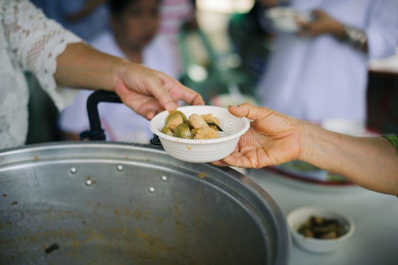Беспризорность концепции: Потребности еды бедных в помощи общества с пожертвованием еды: Бездомные комплектуют вверх еду призрени стоковое фото