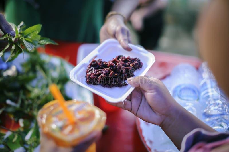 Беспризорность концепции: Потребности еды бедных в помощи общества с пожертвованием еды: Бездомные комплектуют вверх еду призрени стоковые фото