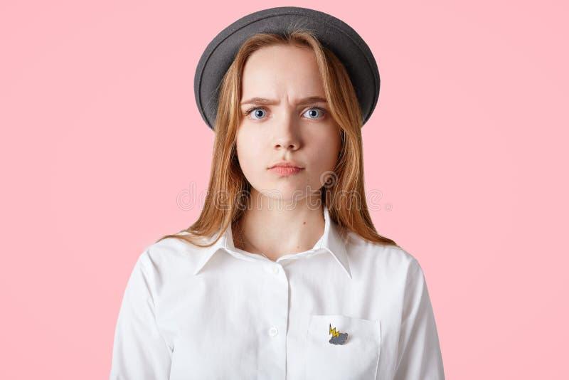 Беспристрастная съемка сварливой унылой серьезной женщины носит элегантную черную шляпу и белая блузка, смотрит сразу в камеру, и стоковые фотографии rf